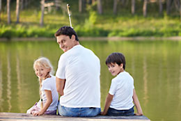 Young family sitting on dock